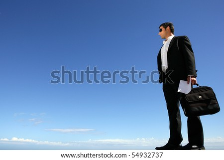 Young businessman in suit with sunglasses - stock photo