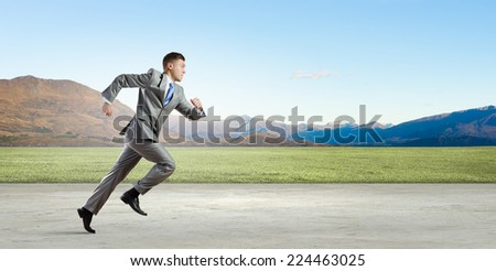 Young businessman in suiut running on countryside road - stock photo