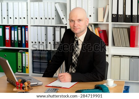 young businessman in the office is looking friendly in to the camera