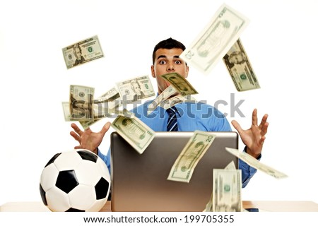 Young businessman in the office is surprised by the rain of money - stock photo