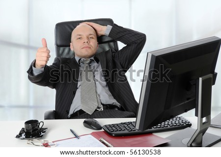 young businessman in the office shows the thumb.