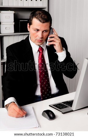 Young businessman in the office with a telephone. Seated at a desk.