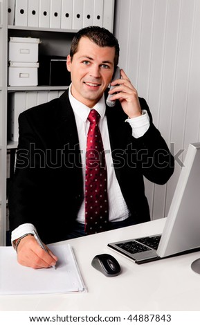 Young businessman in the office with telephone - stock photo