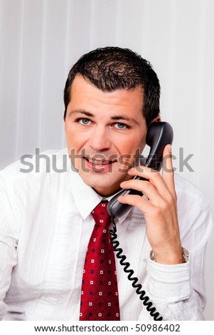 Young businessman in the office with telephone