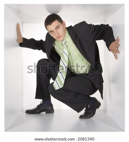 young businessman in the white cube - stock photo