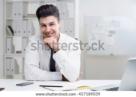 Young businessman in white shirt sitting at his office desk smiling to camera. Concept of corporate business and happiness