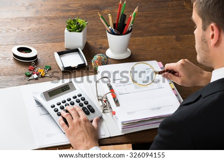 Young Businessman Inspecting Invoice With Magnifying Glass And Calculator At Desk - stock photo
