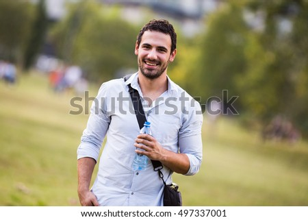 Young businessman is drinking water and resting from work at the park.Businessman drinking water