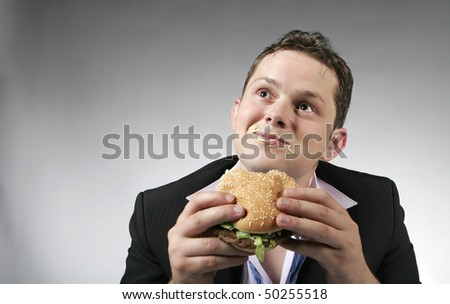 Young businessman is enjoying a hamburger for lunch. Studio shot