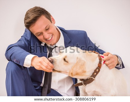 Young businessman is feeding his lovely dog. - stock photo