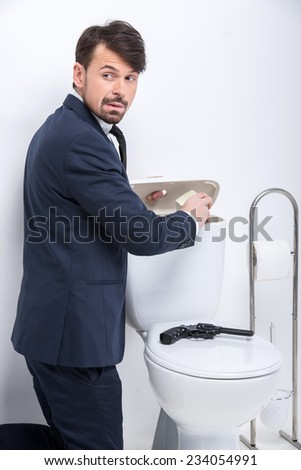Young businessman is hiding money in the toilet tank. A gun on the toilet. - stock photo