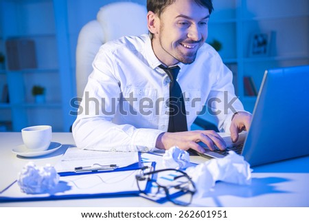 Young businessman is looking at the laptop and smiling - stock photo