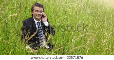 young businessman is out of office in a field - stock photo
