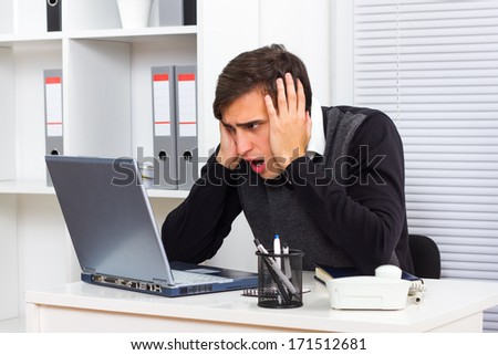 Young businessman is shocked by something he sees on his laptop monitor,Shocked businessman - stock photo