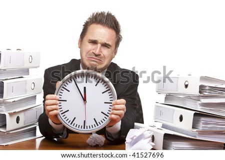 Young businessman is sitting on desk and crying because of unmanageable work and time pressure. Isolated on white. - stock photo