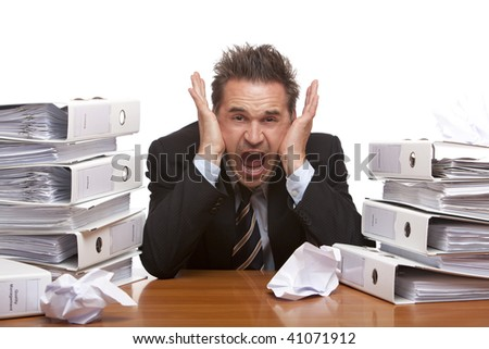 Young businessman is sitting on desk and screaming because of unmanageable work. Isolated on white.