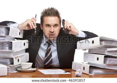 Young businessman is sitting on desk betweent folder stacks and having two telephones on his ears.  Isolated on white.
