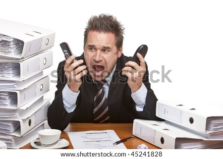 Young businessman is sitting on desk betweent folder stacks and screams into two telephones.  Isolated on white. - stock photo