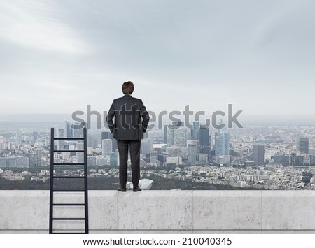 Young businessman is standing on the edge of the skyscraper. A concept of achievement. - stock photo