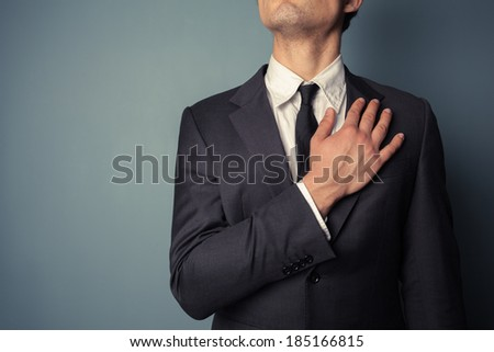 Young businessman is swearing allegiance with his hand on his chest - stock photo