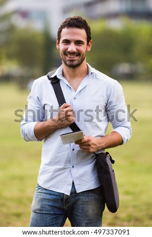 Young businessman is using digital tablet while standing in the park.Businessman using digital tablet outdoor