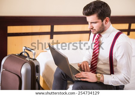 Young businessman is using laptop while sitting at the hotel room with suitcase. - stock photo