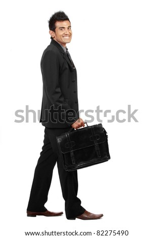 young businessman is walking and smiling to the camera. isolated over white background - stock photo