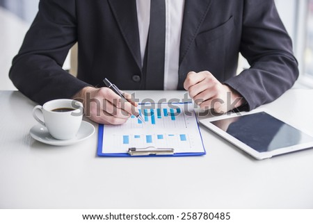 Young businessman is working with papers and drinking coffe. - stock photo
