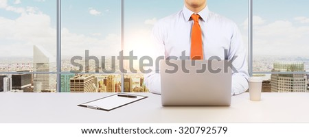 Young businessman is working with the laptop. Modern Panoramic office or work place with New York city view. - stock photo