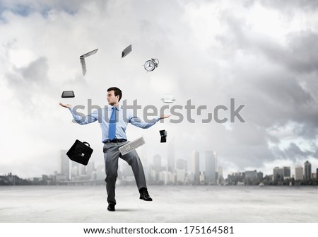 Young businessman juggling with business items against urban scene - stock photo
