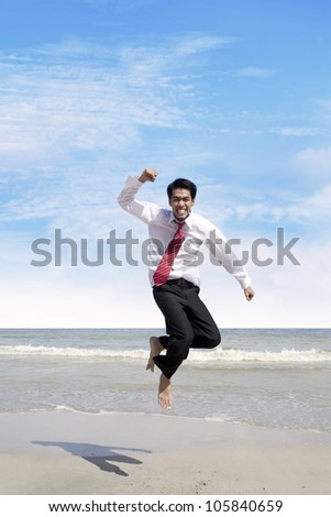 Young businessman jumping at the beach to celebrate his success - stock photo