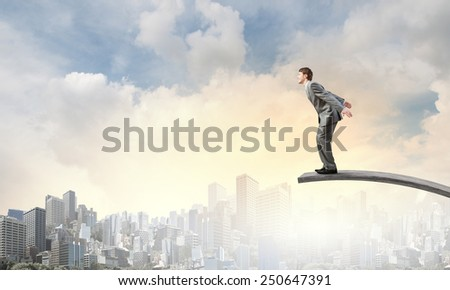 Young businessman jumping from springboard in to deep - stock photo