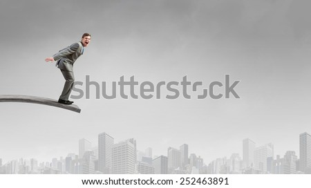Young businessman jumping from springboard in to deep