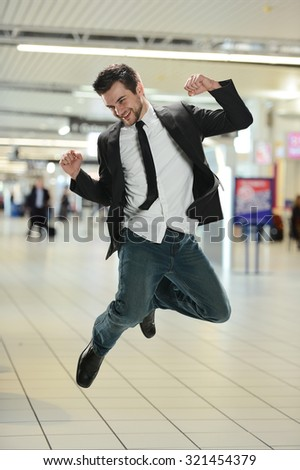 Young Businessman jumping of joy inside the airport terminal - stock photo