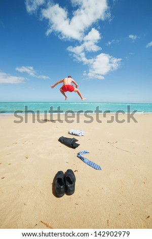 young businessman jumping on the beach after a big deal - stock photo