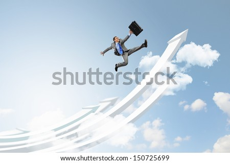 Young businessman jumping on white arrows. Growth concept - stock photo