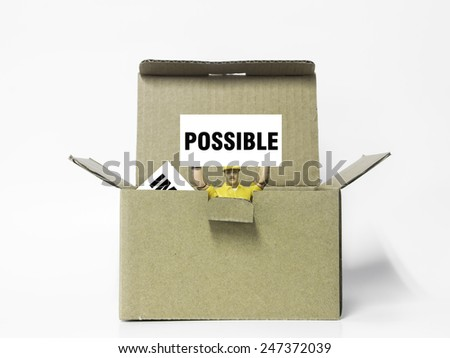 "Young businessman jumping out box holding a sign with the word ""possible"" with the word impossible fall inside the box. Changing the word impossible to possible concept. - stock photo"
