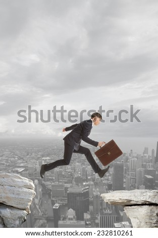 Young businessman jumping over rocks with gap concept - stock photo