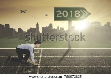 Young businessman kneeling on the start line with numbers 2018 on the signpost. Shot at sunrise time