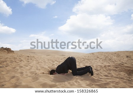 Young businessman kneeling with his head in a hole in the sand - stock photo