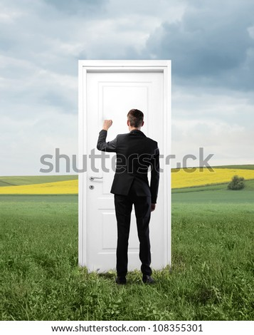 Young businessman knocking at an entrance door on a green meadow - stock photo