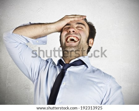 Young businessman laughing with hand on the head  - stock photo