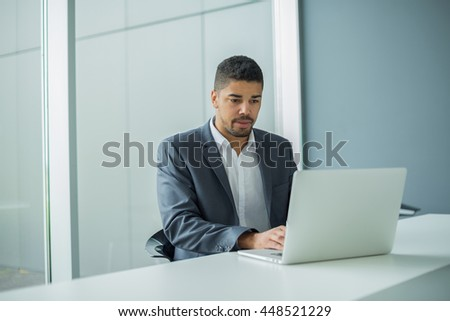 Young businessman lawyer with laptop, alone in big bright conference room. - stock photo