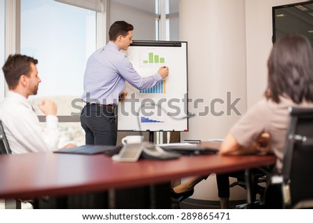 Young businessman leading a meeting with some of his co-workers in a conference room - stock photo