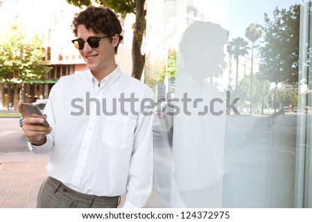 Young businessman leaning on a glass wall in the city wearing shades and using a smart phone and smiling.