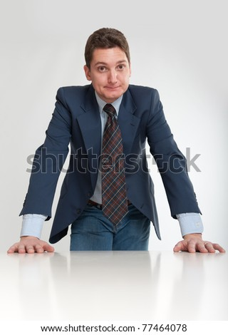 Young businessman leaning on a white desk