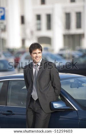 Young businessman leaning on his car