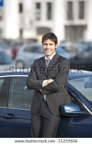 Young businessman leaning on his car - stock photo