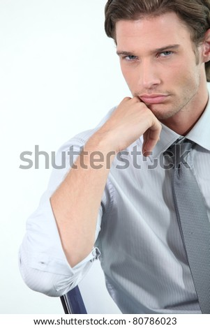 Young businessman leaning on his chair - stock photo