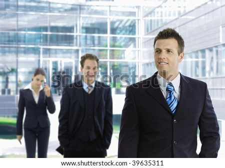 Young businessman leaving office building aong other businesspeople in the background. - stock photo